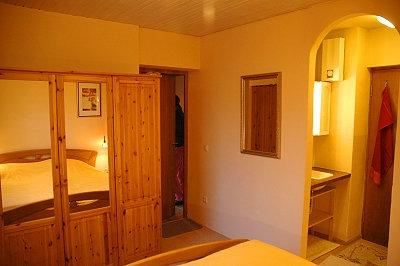 Doppelbett, großer Kleiderschrank, Spiegel und der Blick zum Waschbecken